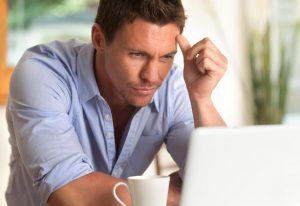 mężczyzna wpatrujący się w ekran laptopa