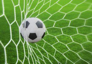 piłka wpadająca do bramki podczas meczu futbolowego