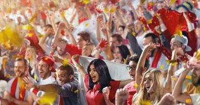 Duża grupa ludzi kibicujących na stadionie piłkarskim