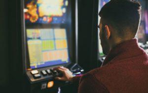 Młody mężczyzna przed automatem do gier