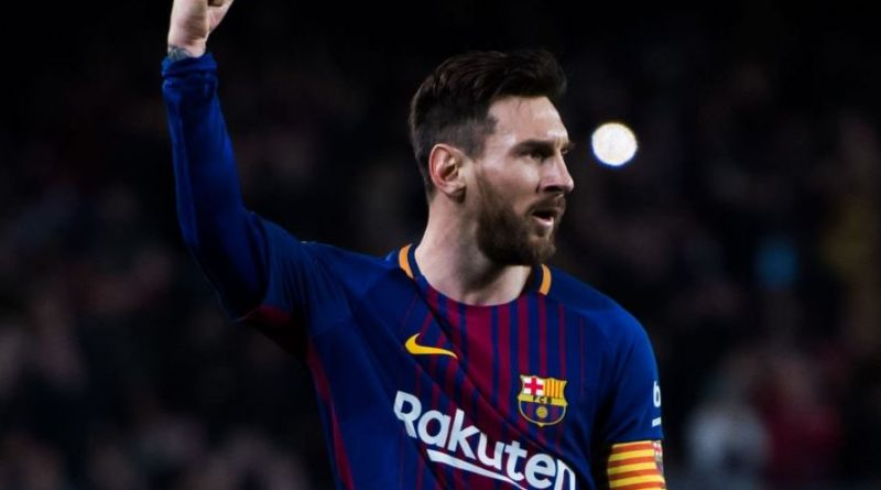 Lionel Messi z uniesioną dłonią na stadionie piłkarskim