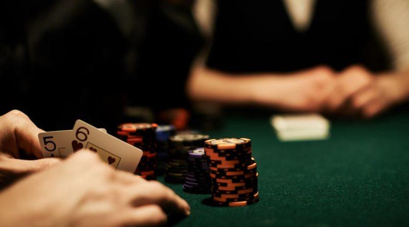 stół pokerowy z żetonami i kartami, otoczony przez kilka osób