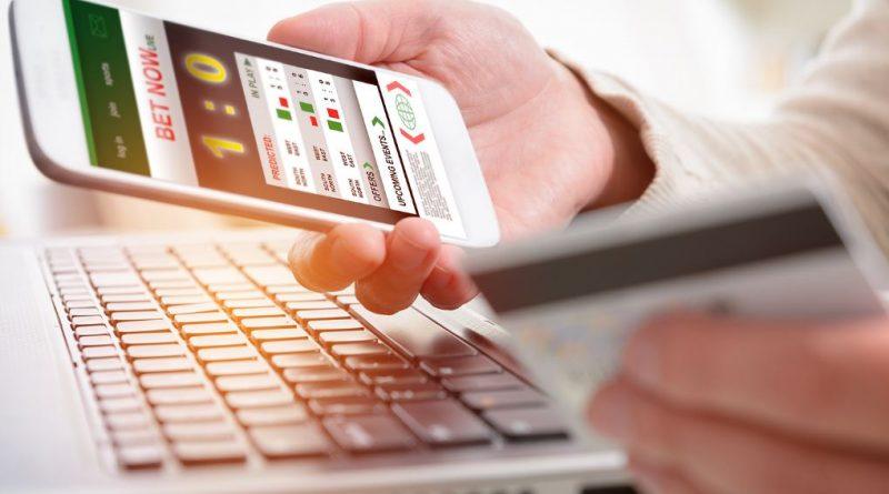 telefon z aplikacją do obstawiania zakładów wzajemnych i karta płatnicza