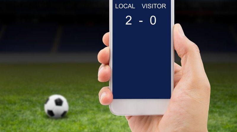 dłoń ze smartfonem z wynikiem meczu, w tle boisko piłkarskie