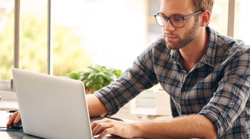 młody mężczyzna w kraciastej koszuli pracuje na laptopie