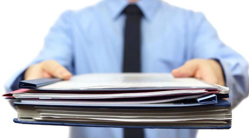 męzczyzna w niebieskiej koszuli podający w stronę obiektywu stos dokumentów