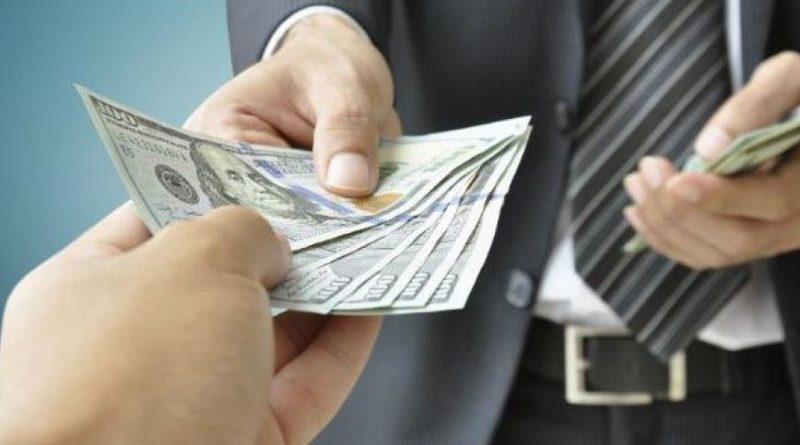 mężczyzna w garniturze przekazujący plik banknotów w stronę obiektywu