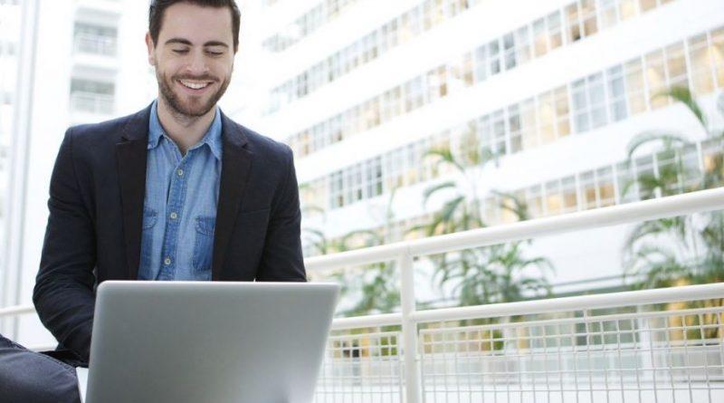 Młody uśmiechnięty mężczyzna z laptopem na kolanach