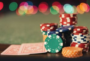 stos żetonów i karty do gry na pokerowym stole