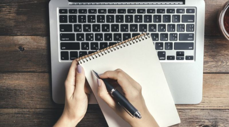 klawiatura laptopa i leżący na niej notatnik oraz długopis, oba trzymane przez kobiecie dłonie