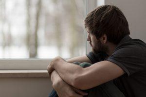 młody mężczyzna obejmujący rękoma kolana i wpatrujący się w okno