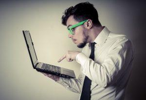 mężczyzna w białej koszuli trzymający laptopa