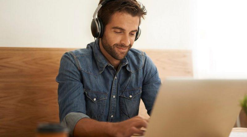 młody mężczyzna ze słuchawkami na uszach pisze na laptopie