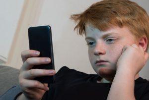 chłopiec trzymający w dłoni telefon komórkowy