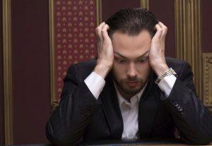 Młody zmartwiony mężczyzna pochylony nad stołem pokerowym