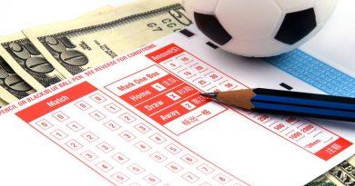 kupon bukmacherski i ołówek, plik banknotów i piłka na białym tle