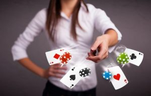 karty do gry i żetony pokerowe rzucane w stronę obiektywu przez młodą dziewczynę