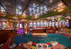 wnętrze kasyna ze stołami pokerowymi i automatami do gier
