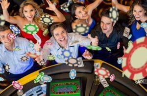 Grupa młodych ludzi w kasynie przy stole pokerowym, na których z góry sypią się żetony