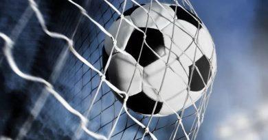 piłka w bramce na tle oświetlonego stadionu piłkarskiego
