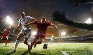 gracz futbolowy w czerwonej koszulce przed wbiciem gola do bramki