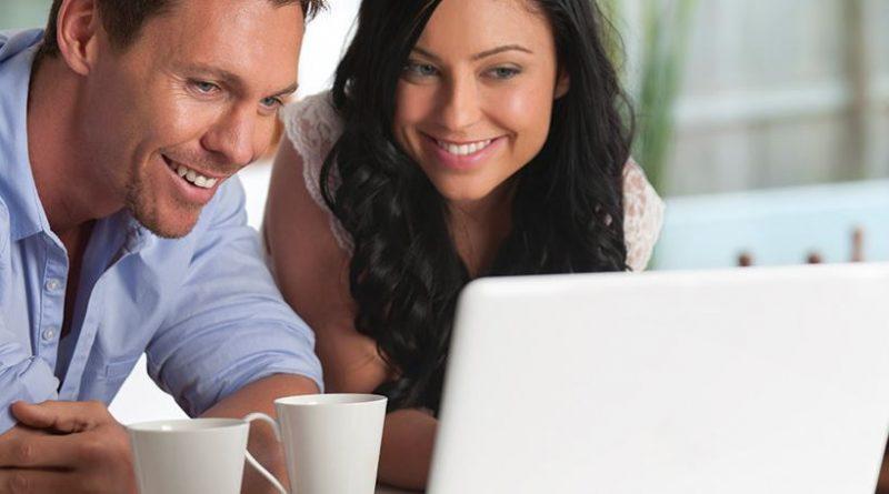 Uśmiechnięci mężczyzna i kobieta przed laptopem