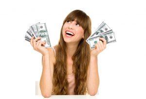młoda uśmiechnięta kobieta trzymająca w obu dłoniach pliki banknotów