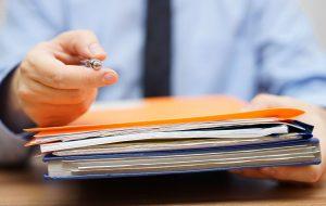 mężczyzna kierujący w stronę obiektywu plik dokumentów i długopis