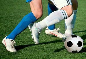 nogi dwóch mężczyzn kopiących piłkę na boisku