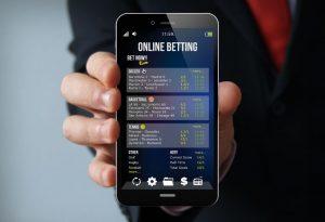 dłoń trzymająca telefon z aplikacją do typowania