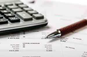 długopis i kalkulator na kartce z danymi