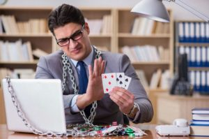 mężczyzna z kartami do pokera skuty łańcuchem