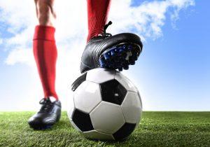 stopy piłkarza i piłka do futbolu na murawie