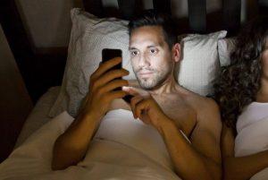młody męzczyzna z telefonem leżący w łóżku